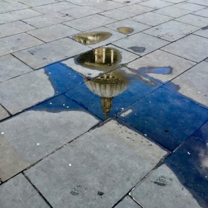 A reflection of St Paul's in a pavement puddle